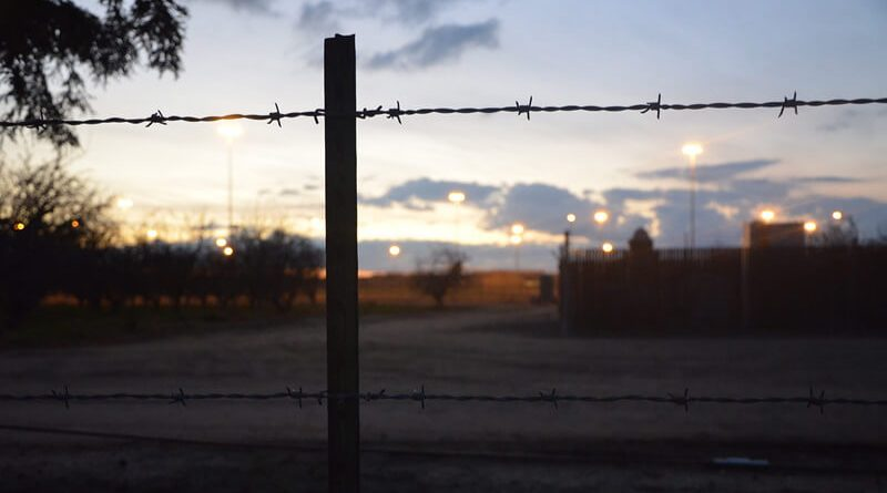 Photo of Chowchilla Valey State Prison through barbed wire